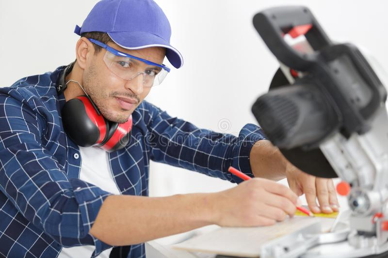 Handsome young man carpenter using circular saw royalty free stock images