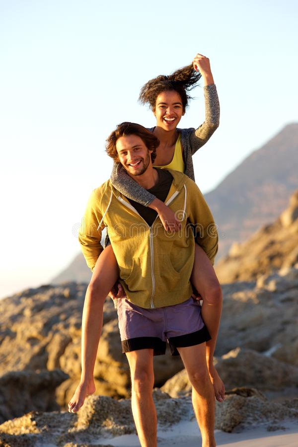 Handsome young man carrying young woman on back stock photos