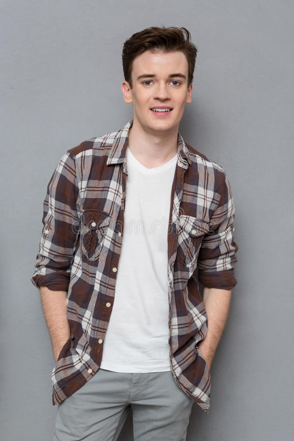 Handsome young man in checkered shirt posing and smiling stock photos
