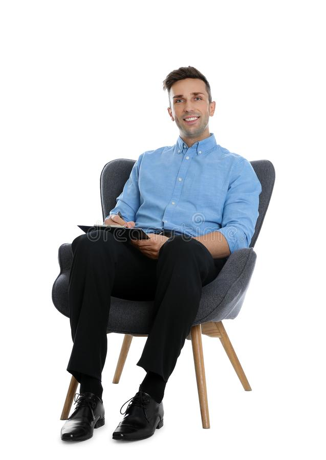 Handsome young man with clipboard sitting in armchair on background stock images