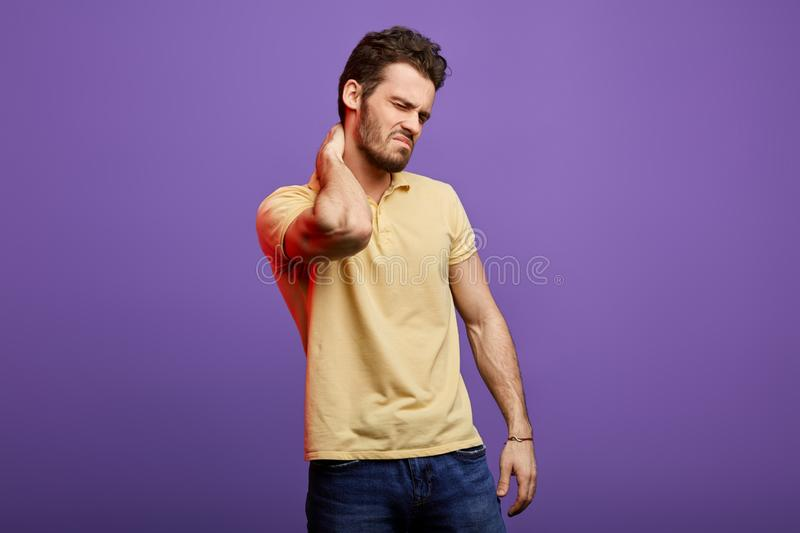 Handsome young man suffering from severe , prolonged neck pain stock images