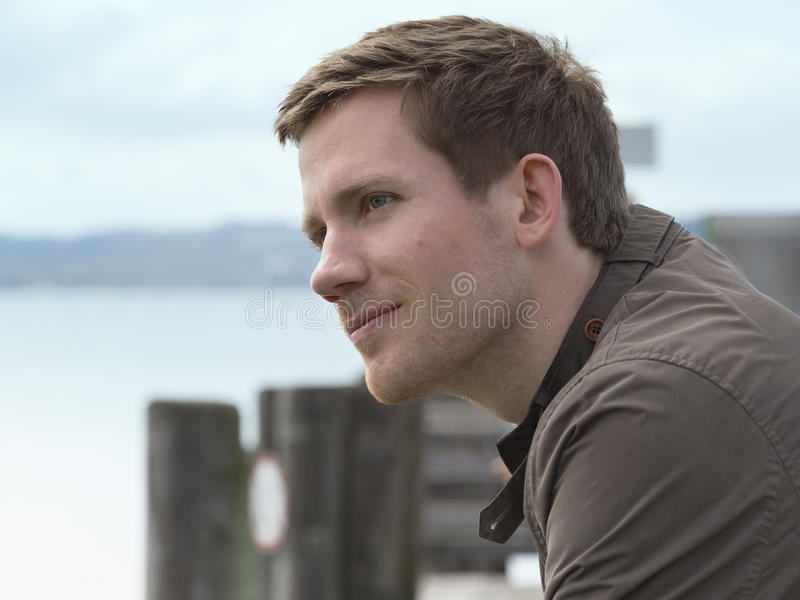Handsome young man on a coastal pier. Standing overlooking the water with a charismatic smile on his face and thoughtful expression, close up side view stock photos