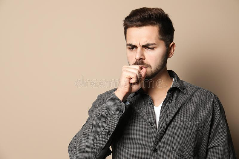 Handsome young man coughing against. Space for text. Handsome young man coughing against color background. Space for text stock photos