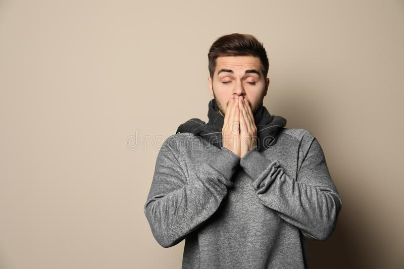 Handsome young man coughing against color background. Space for text stock images