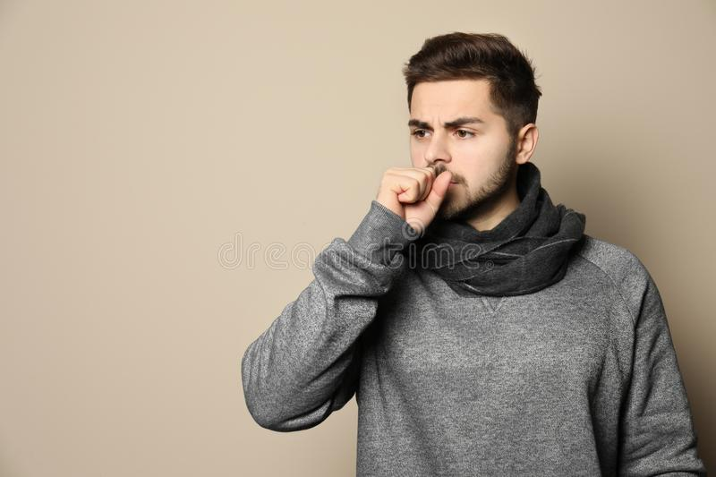 Handsome young man coughing against color background. Space for text royalty free stock image