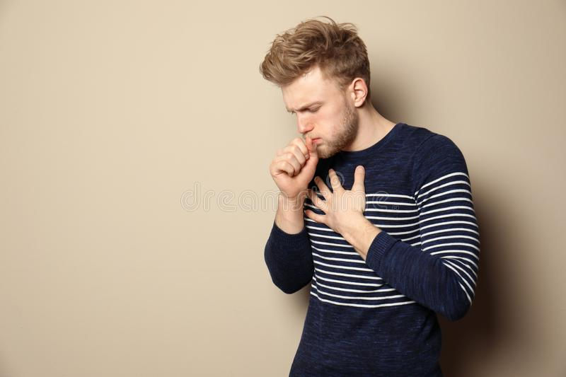 Handsome man coughing against color background. Handsome young man coughing against color background. Space for text stock photos