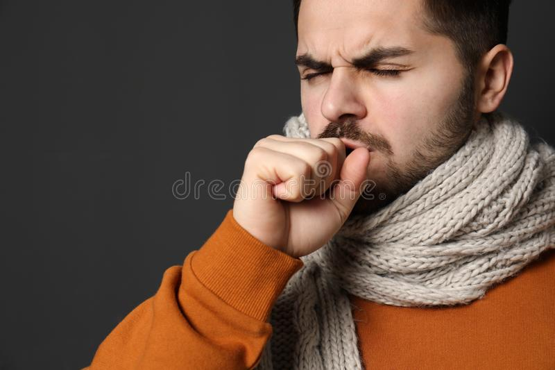 Handsome young man coughing against dark background. Space for text stock photo