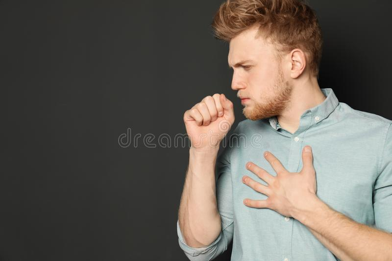 Handsome young man coughing against dark background. Space for text royalty free stock photography