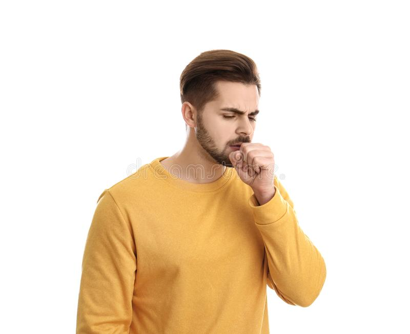 Handsome young man coughing. Against white background royalty free stock photography