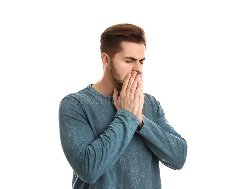 Young man coughing against white background. Handsome young man coughing against white background royalty free stock image