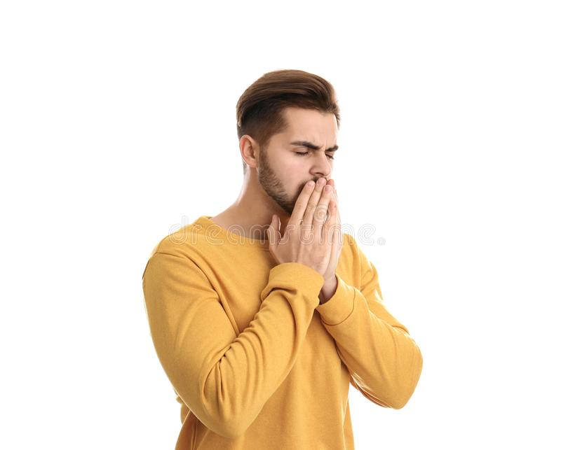 Young man coughing against white background. Handsome young man coughing against white background stock image