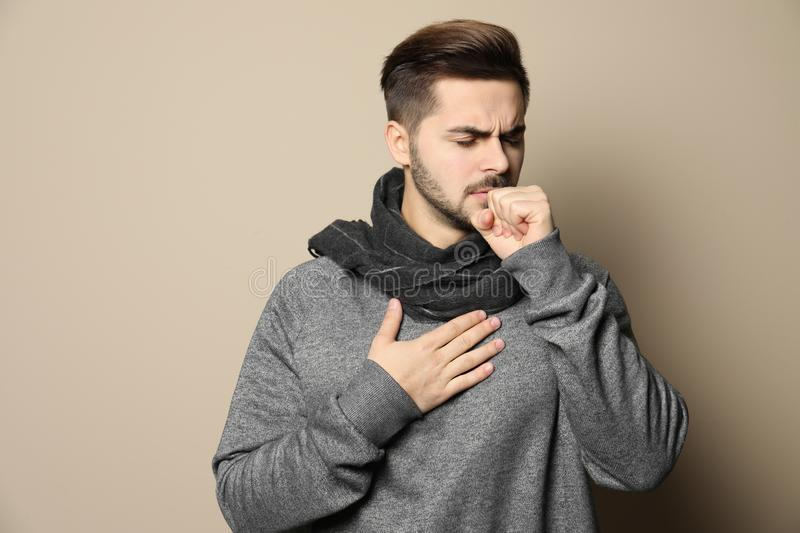Handsome young man coughing. Against color background royalty free stock photography