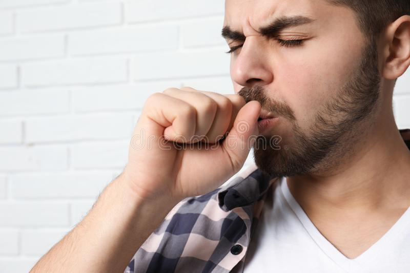 Handsome young man coughing near wall. Handsome young man coughing near brick wall stock photography