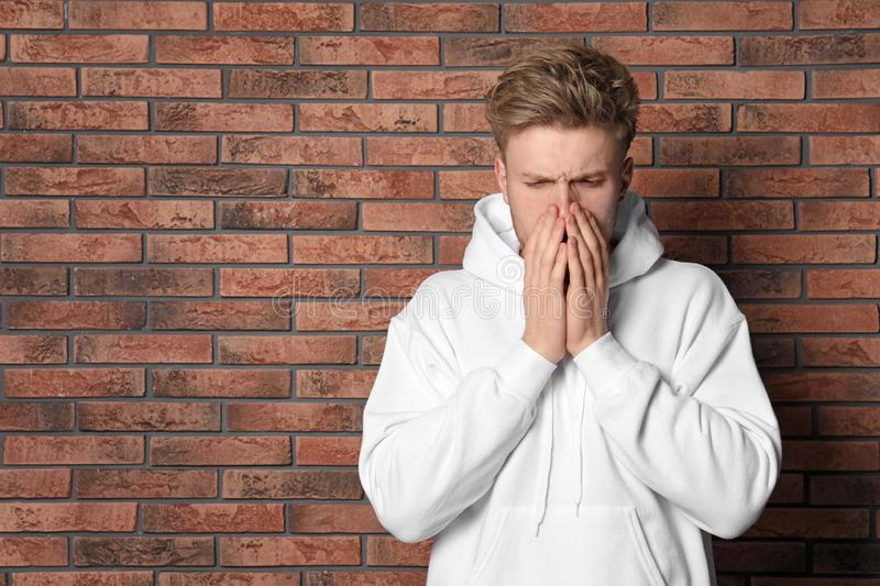 Handsome young man coughing near brick wall. Space for text royalty free stock photo