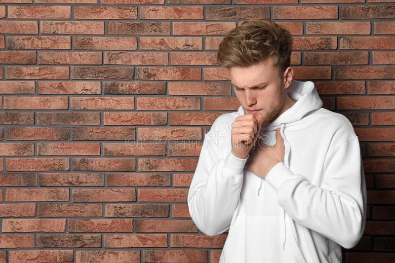 Handsome young man coughing near brick wall. Space for text stock images
