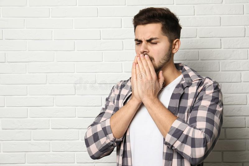 Handsome young man coughing near brick wall. Space for text stock image