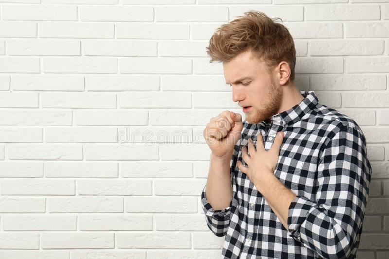 Handsome young man coughing near brick wall. Space for text royalty free stock photos