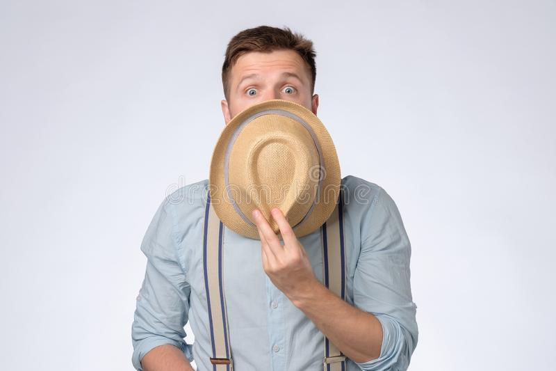 Handsome young man covering face with hat looking shocked and amazed. stock images
