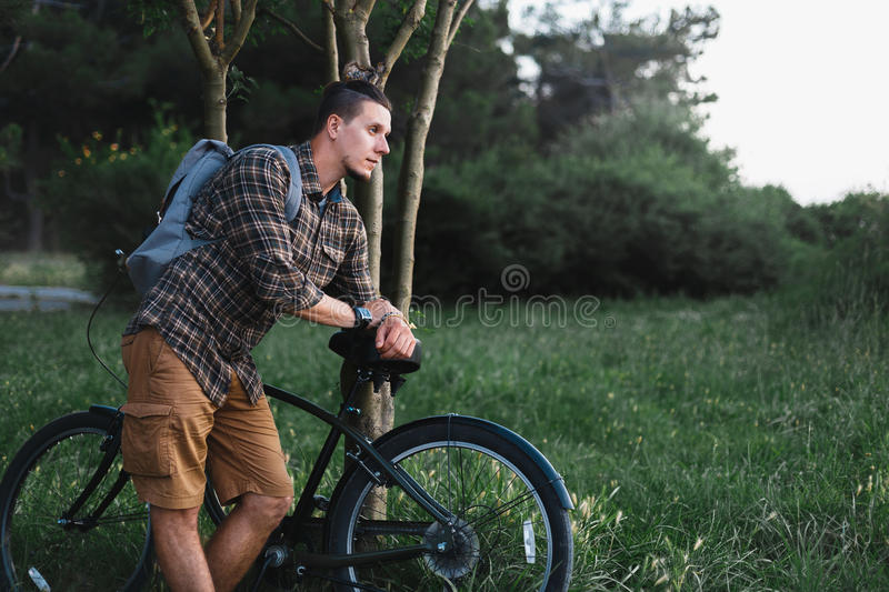 Handsome Young Man Cyclist Standing Resting With Bicycle Near Tree In Summer Park Resting Recreation Travel Destination Concept. Young man cyclist with backpack royalty free stock photo
