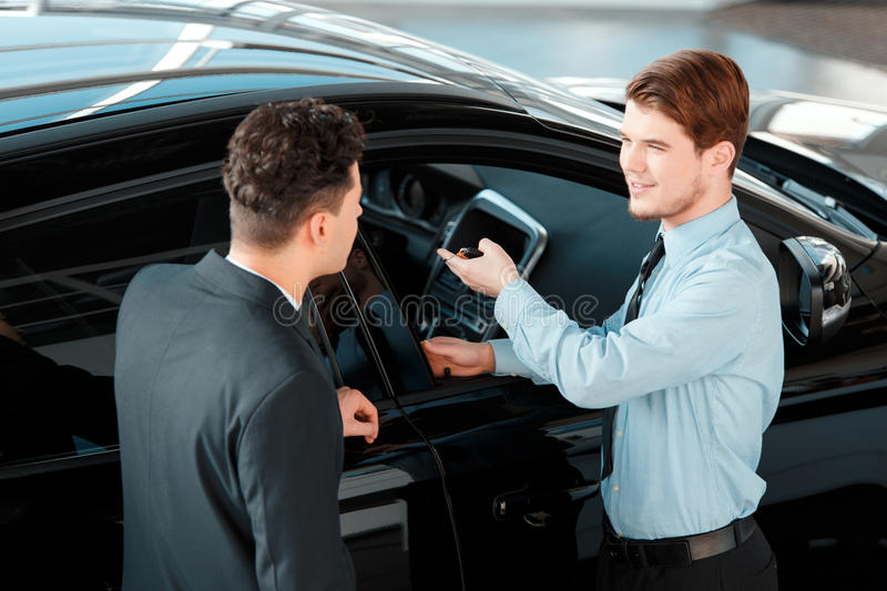 Handsome young man in dealership royalty free stock images