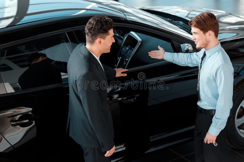 Handsome young man in dealership stock photo