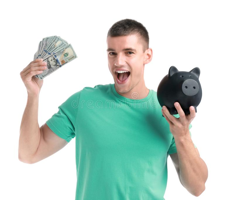 Handsome young man with dollars and piggy bank. On white background stock photo