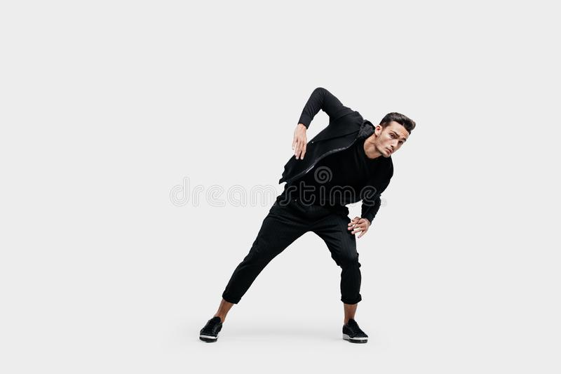 Handsome young  man dressed in a black clothes is dancing street dance. He makes stylized movements with his hands.  stock images