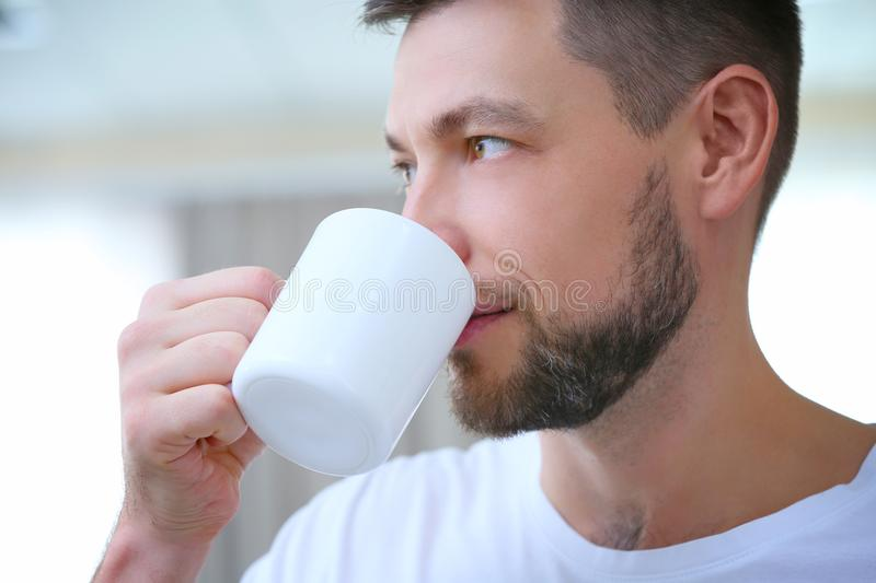 Handsome young man drinking coffee at home, stock photos
