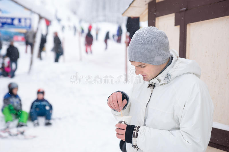 Handsome young man drinking coffee in winter. As he stands outdoors at a ski resort stirring in the sugar, upper body close up view with other people as a blur royalty free stock photos