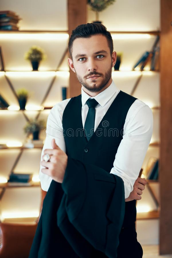 Handsome young man in elegant suit in modern luxury interior royalty free stock images