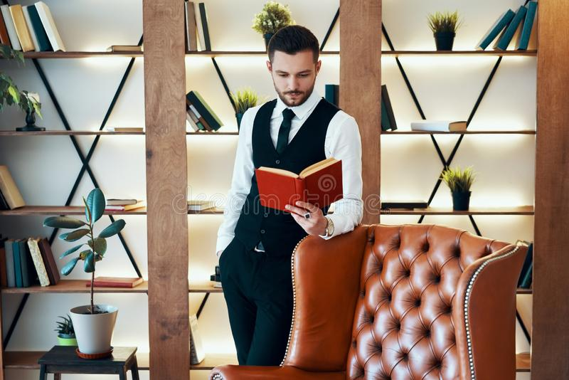Handsome young man in elegant suit reading a book in modern luxury interior stock photo