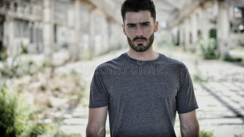 Handsome young man in empty warehouse stock photography