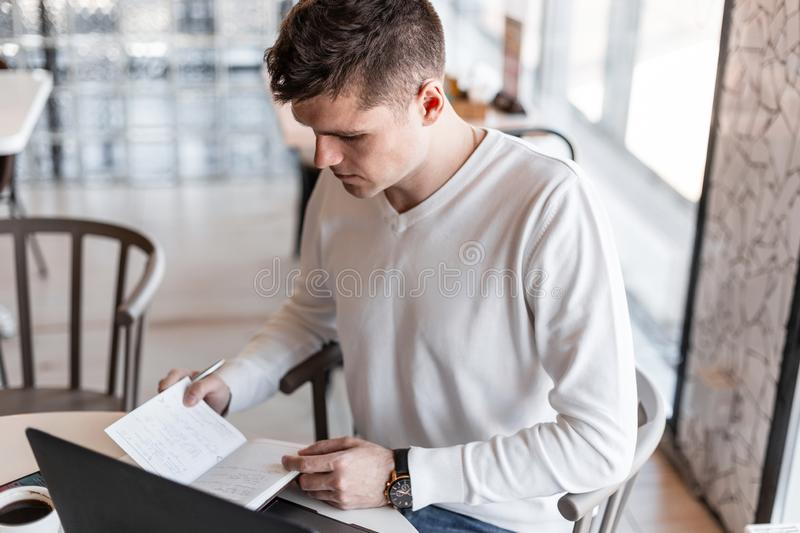 Handsome young man entrepreneur with a laptop in a stylish shirt is writing in a notebook sitting in a cafe. Professional blogger guy writes down ideas. Remote royalty free stock photography