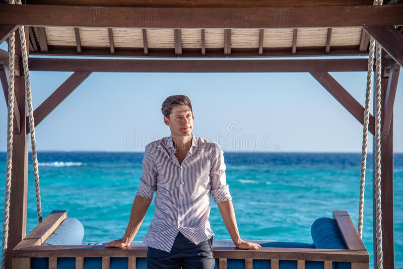 Handsome young man in expensive shirt sitting on the swing and water villas at the tropical island luxury resort. In Maldives royalty free stock photos