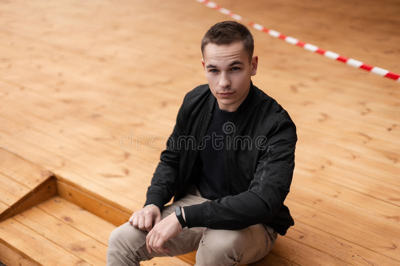 Handsome young man with a fashionable hairstyle in a black stylish jacket in vintage beige trousers relaxes sitting indoors. On wooden steps. Cute modern royalty free stock images