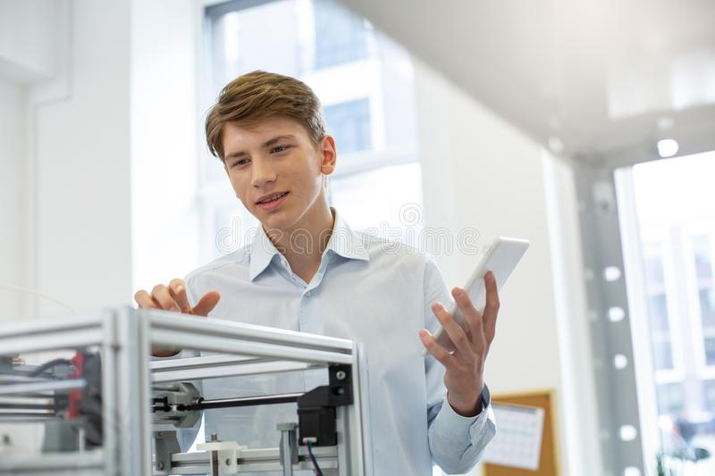 Handsome young man figuring out 3D printer configurations. Practical knowledge. Pleasant young man figuring out 3D printer configurations while holding a tablet royalty free stock photography
