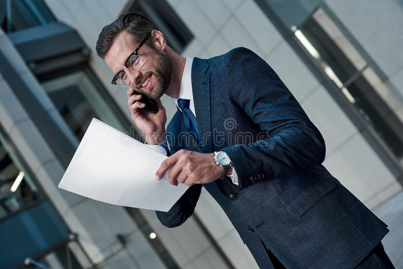 Handsome young man in full suit reading contract while standing royalty free stock image