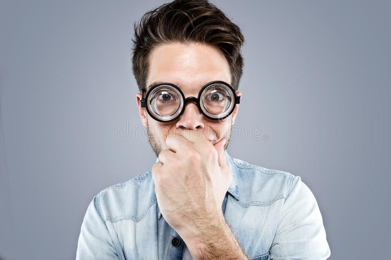Handsome young man with funny glasses joking and making funny face over gray background. stock image