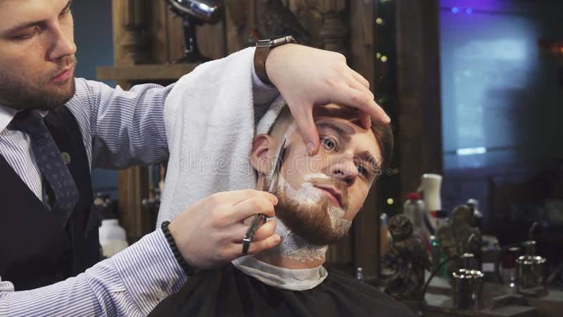 Handsome young man getting his beard shaved at the barbershop stock images