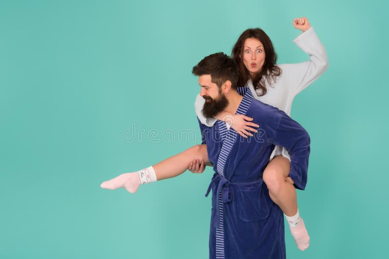 Handsome young man giving his girlfriend piggyback ride. Couple in bathrobes having fun turquoise background. Lets stay. Handsome young men giving his girlfriend royalty free stock images