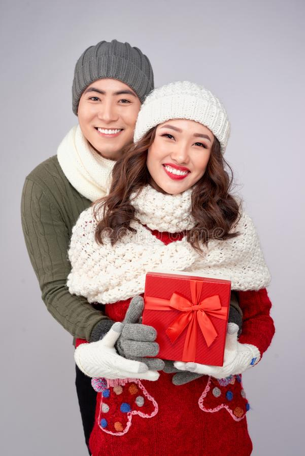 Handsome young man giving present to beautiful woman. Christmas time royalty free stock images