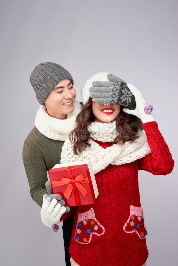 Handsome young man giving present to beautiful woman. Christmas time stock image