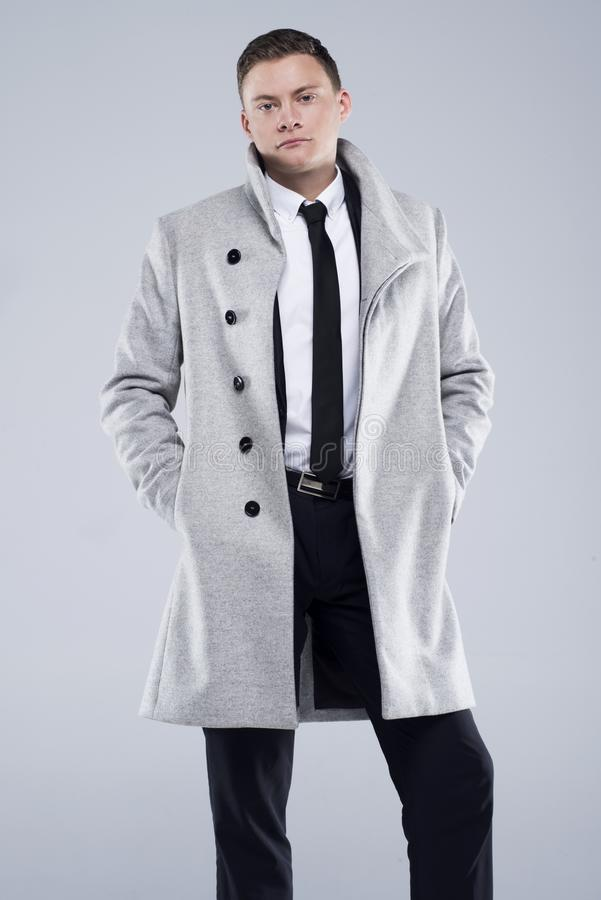 Handsome young man in a gray coat and black suit stock photography