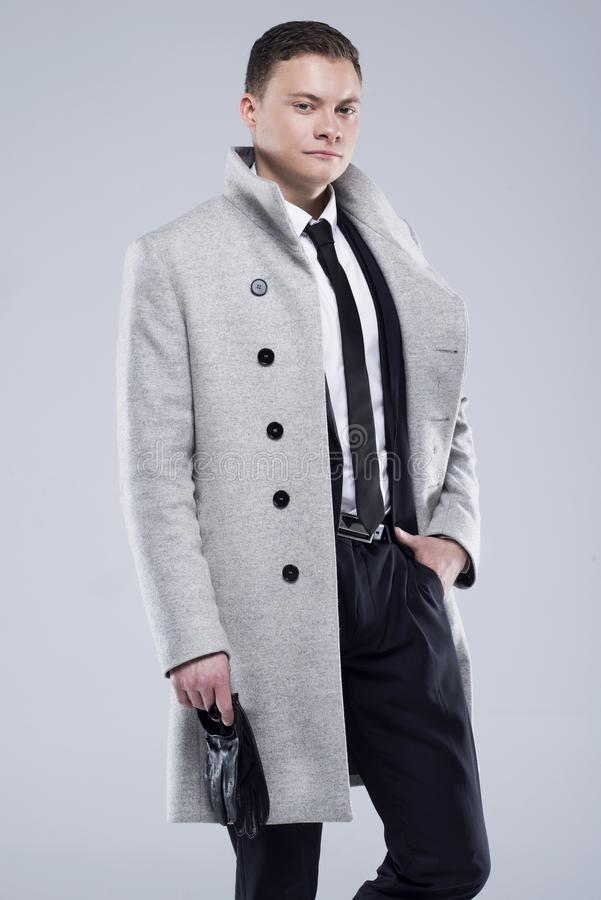 Handsome young man in a gray coat and black suit royalty free stock images