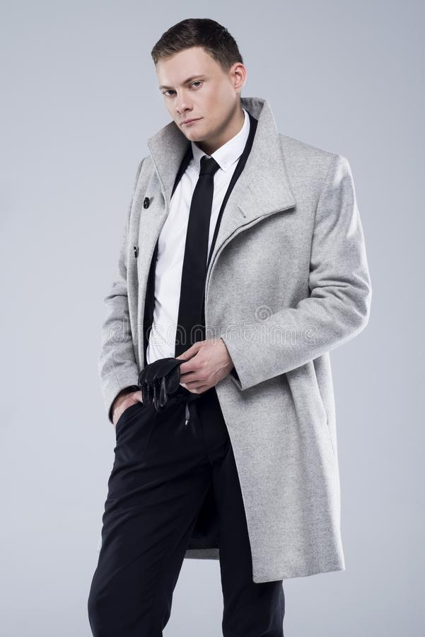 Handsome young man in a gray coat and black suit royalty free stock image