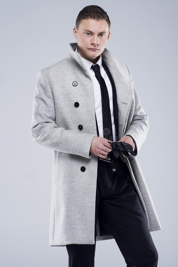 Handsome young man in a gray coat and black suit stock images
