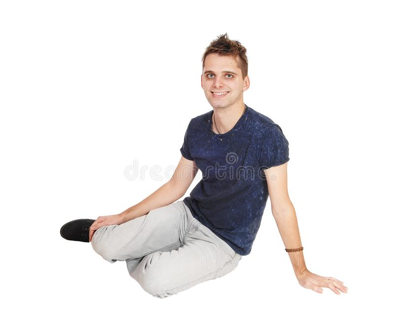 Young man sitting on floor smiling into the camera royalty free stock photo
