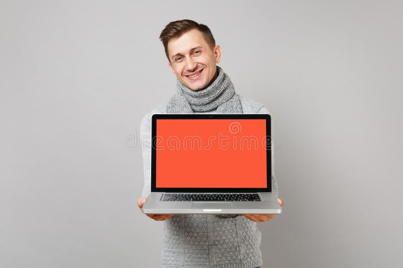 Handsome young man in gray sweater, scarf holding laptop pc computer with blank empty screen isolated on grey background royalty free stock images