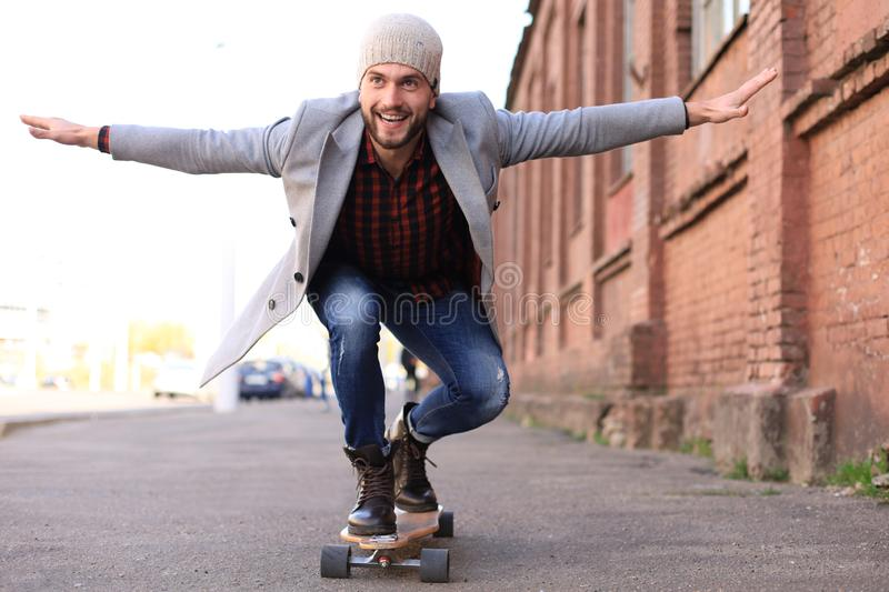 Handsome young man in grey coat and hat on longboard on the street in the city. Urban skateboarding concept stock photography