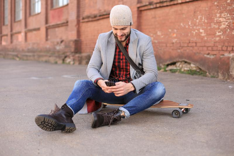 Handsome young man in grey coat and hat sitting on the longboard on the street in the city. Urban skateboarding concept stock photos